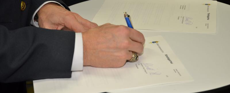 Человек подписывает документ о передаче денег